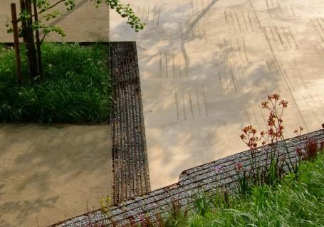 El pavimento está hecho principalmente de hormigón coloreado y estampado con un molde improvisado, salvo la sección más baja que está hecha de pavimento agregado estabilizado naturalmente, que favorece la infiltración y el desarrollo del sistema radical de los árboles.